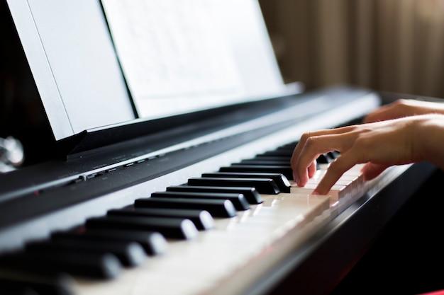Крупный план руки исполнителя классической музыки, играющей на пианино или электронном синтезаторе (фортепианной клавиатуре), размытый фон