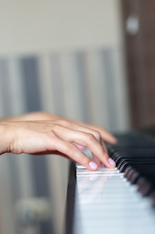 Крупный план руки исполнителя классической музыки, играющей на пианино или электронном синтезаторе (фортепианная клавиатура), девушка на уроке фортепиано