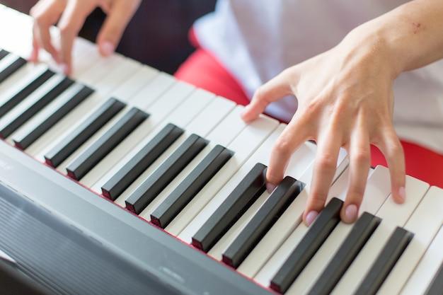 Крупный план руки исполнителя классической музыки, играющей на пианино или электронном синтезаторе (клавиатуре фортепиано), руки берут аккорд
