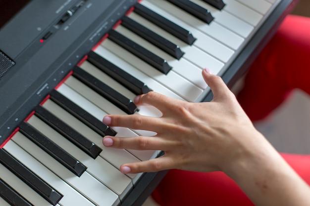 Крупный план руки исполнителя классической музыки, играющего на левой руке на пианино или электронном синтезаторе (фортепианной клавиатуре)