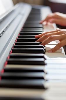 Крупный план руки исполнителя классической музыки, играющей на пианино или электронном синтезаторе (фортепианная клавиатура) на уроке в музыкальной школе