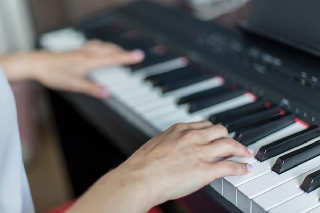 Крупный план руки исполнителя классической музыки, играющей на пианино или электронном синтезаторе (фортепианная клавиатура)