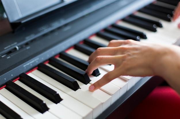 Крупный план руки исполнителя классической музыки, играющей на пианино или электронном синтезаторе (фортепианной клавиатуре), берущей аккорд
