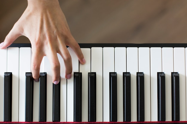 Крупный план руки исполнителя классической музыки, играющей на пианино или электронном синтезаторе (фортепианная клавиатура).