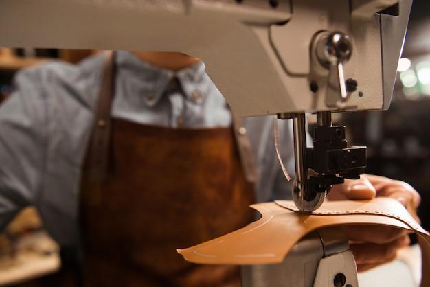Крупным планом сапожник с помощью швейной машины