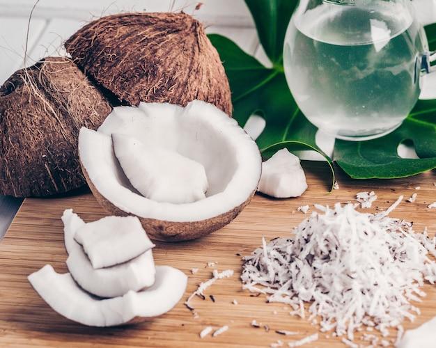 竹の背景に、ココナッツ、ココナッツチップとミルク、モンステラの葉のクローズアップ。ファッションカラーフィルター。
