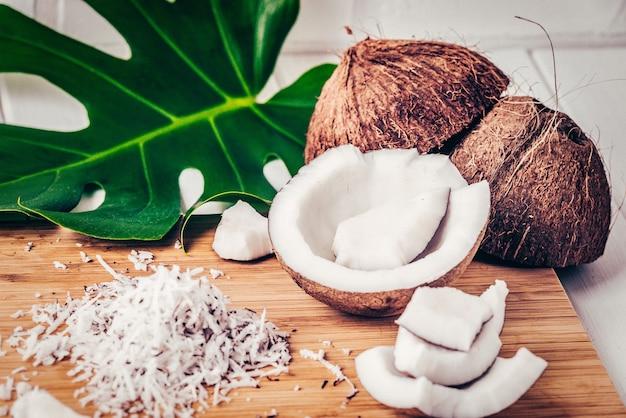 ココナッツのクローズアップ、竹の背景にココナッツチップ、モンステラの葉。ファッションカラーフィルター。