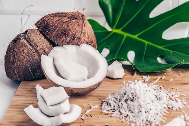 ココナッツのクローズアップ、竹の上のココナッツチップ、モンステラの葉。