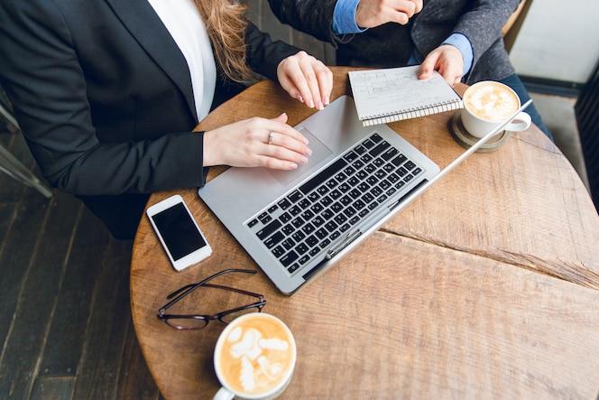 ノートパソコンを押しながらノートパソコンに入力して座っている2人の同僚とコーヒーテーブルのクローズアップ