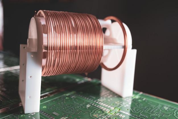 現代の電子機器に対する大きなマイクロ回路上に立っている銅線のコイルの拡大図。強力な発振回路と高周波成分