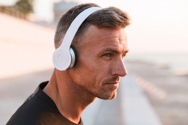 Крупным планом уверенного в себе спортсмена, слушающего музыку