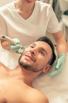 Крупным планом уверенный в себе молодой человек, выглядящий довольным, пока косметолог держит современный инструмент и увлажняет его кожу на щеке