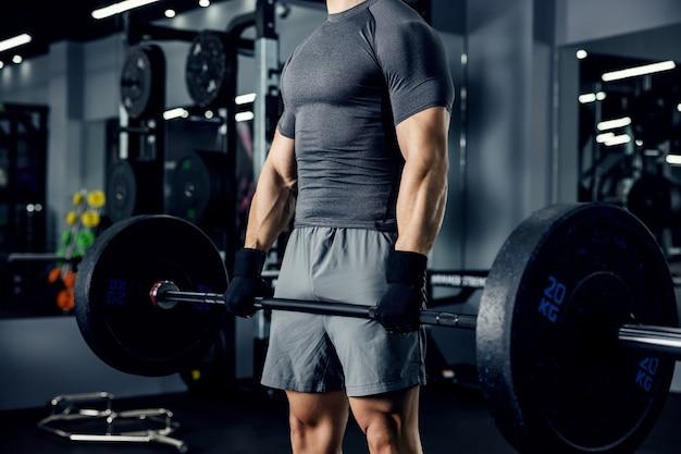 暗い雰囲気のジムでバーベルで上腕二頭筋を構築するハンサムな若いスポーツマンのコアのクローズアップ。スポーツ、フィットネスの概念。