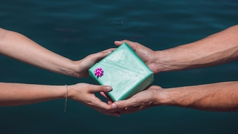 Close-up of a couple's hand holding gift box in front of sea