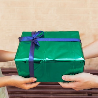 Close-up of a couple's hand holding green gift box