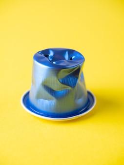 黄色の背景にしわくちゃの使用済みアルミニウムコーヒーカプセルのクローズアップ。青色、リサイクル、側面図