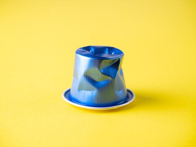 黄色の背景にしわくちゃの使用済みアルミニウムコーヒーカプセルのクローズアップ。青色、リサイクル