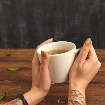 女性の手で緑の香りのよいお茶のカップのクローズアップ