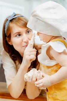 かわいい思いやりのある母親のクローズアップは、彼女のかわいい汚れた娘にフリッターの生地を作る方法を示しています。家庭での子供との共同料理のコンセプト