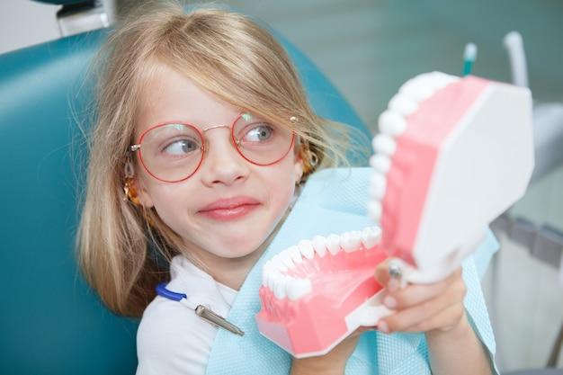 歯の顎のモデルを保持している好奇心旺盛に見えるかわいい面白い女の子のクローズアップ
