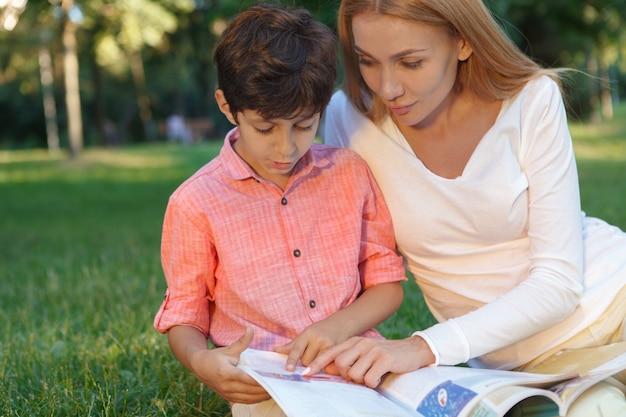 Крупным планом милый маленький мальчик и его учительница, читающая книгу на открытом воздухе, копирование пространства