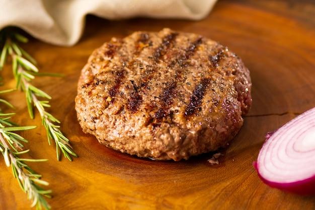 Крупным планом вкусный жареный бургер с фиолетовым луком, розмарина травы на деревянном столе