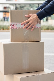 Close-up of a delivery man's hand carrying cardboard box
