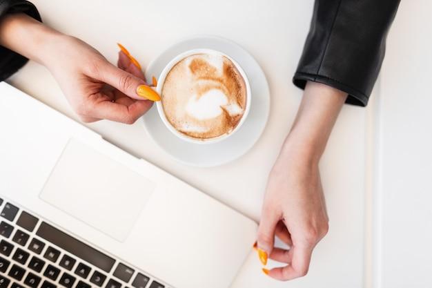 Крупный план рабочего стола с чашкой горячего кофе и современным ноутбуком, позади сидит девушка в черной стильной одежде. деловая женщина начала кофе-брейк. удаленная работа.