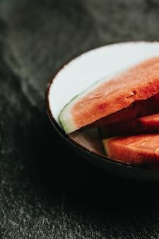 Закройте блюдо, наполненное арбузом, над черным мраморным столом, свежие продукты, велнес, здоровую пищу