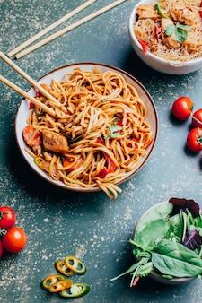 皿に肉と野菜を入れた中華麺と緑の表面に箸を置いた中華麺のクローズアップ