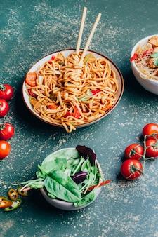 皿に肉と野菜を入れた中華麺と緑の上の箸のクローズアップ