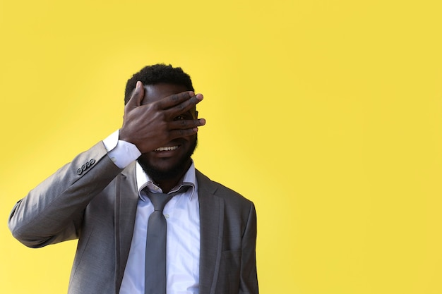 스튜디오 노란색 배경에서 퍼프 머리에 손으로 불쾌한 아프리카 미국 남자의 근접