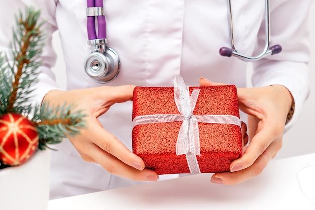 빨간 선물 상자를 들고 의사의 손 클로즈업. 크리스마스, 새 해 및 의료 개념입니다.