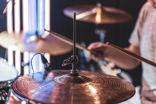 드러머가 연주할 때 흐린 배경에 있는 드럼 심벌즈의 클로즈업.