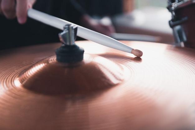 Крупный план руки барабанщика, держащей белые барабанные палочки, сидя за барабанной установкой.