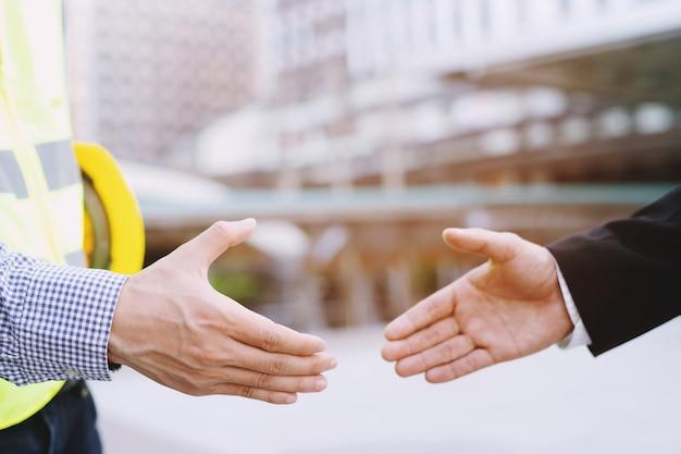 エンジニアリングの男性計画のクローズアップ建設プロジェクトの労働者が2人のビジネスマンの間で握手します。建物の屋外。