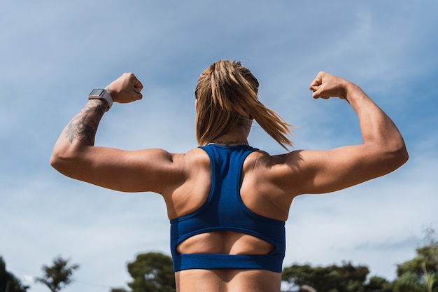 屋外で完璧な上腕二頭筋を持つ女性のボディビルダーのクローズアップ。