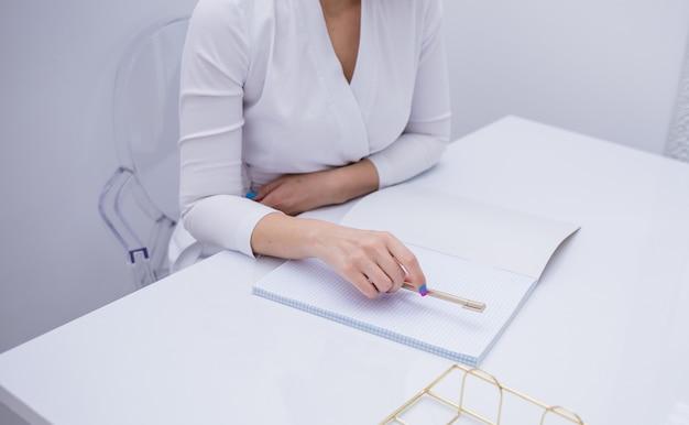 책상에 있는 공책에 메모를 하는 여성 의사의 클로즈업