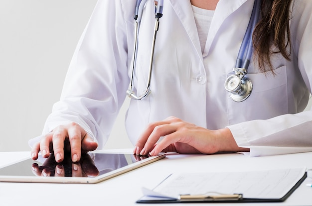 Конец-вверх женского доктора используя цифровую таблетку и медицинское заключение на столе