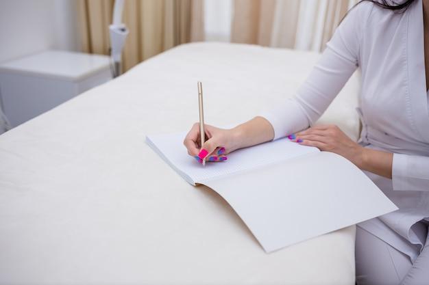 ノートに書いている女性医師のクローズアップ