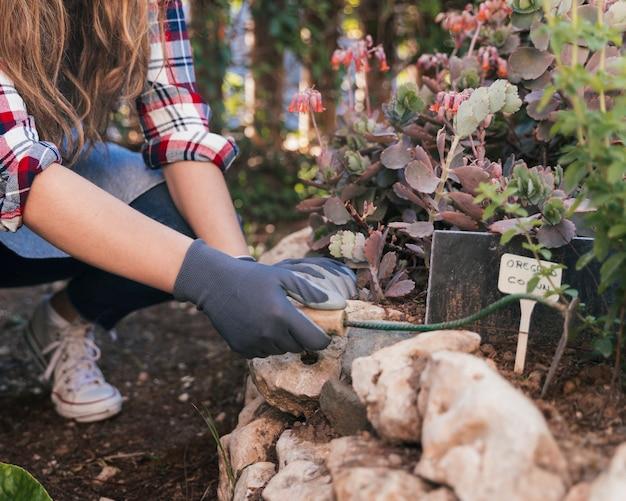 庭で手鍬で土を掘る女性庭師のクローズアップ
