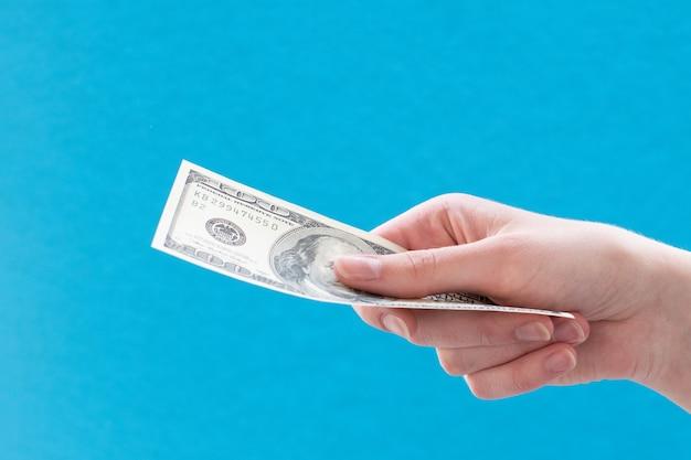 青に対して100ドル札を与える女性の手のクローズアップ