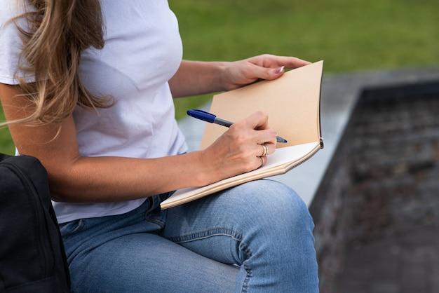 Крупным планом женской руки, которая пишет в записной книжке, сидя на улице в парке.