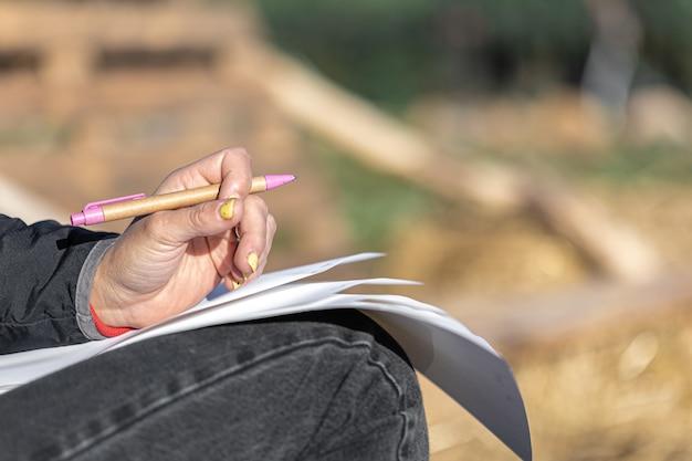 노란 매니큐어를 한 여성의 손을 클로즈업하면 바깥쪽 흐릿한 배경에 펜과 종이가 있고 복사 공간이 있습니다.