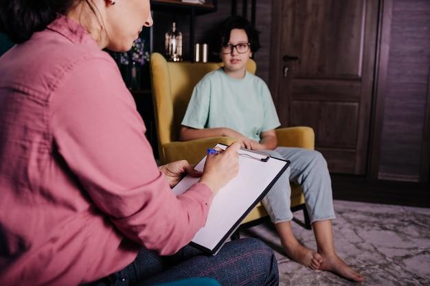 椅子に座って10代の少女のレセプションを録音している女性心理学者のクローズアップ