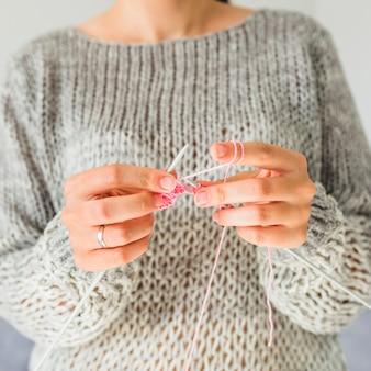 Крупный план руки женщины вязание крючком с розовой нитью
