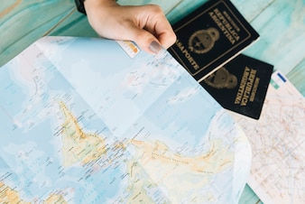 Close-up of a female's hand holding map and passports