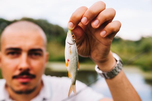 Крупный план рыбака, державшего недавно пойманную рыбу