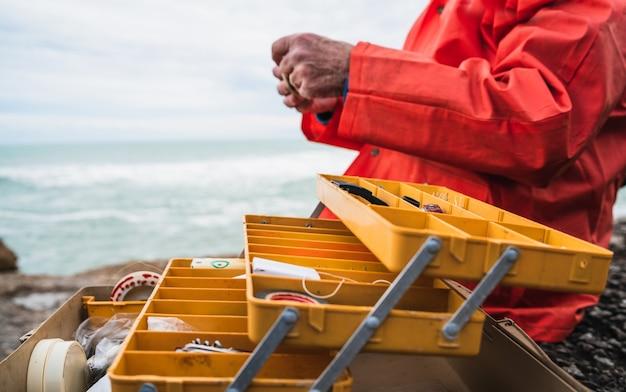 釣り道具箱で餌をつけている漁師の拡大図。釣りとスポーツのコンセプト。