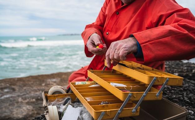 釣り道具箱で餌をつけている漁師のクローズアップ。釣りとスポーツのコンセプト。